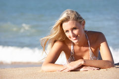 Νέα γυναίκα που κάνει ηλιοθεραπεία στην παραλία Στοκ εικόνες με δικαίωμα ελεύθερης χρήσης