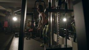 Νέα γυναίκα που κάνει την άσκηση για πίσω στη μηχανή κατάρτισης απόθεμα βίντεο