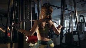 Νέα γυναίκα που κάνει την άσκηση για πίσω στη μηχανή κατάρτισης φιλμ μικρού μήκους