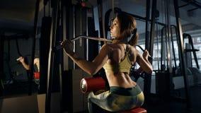 Νέα γυναίκα που κάνει την άσκηση για πίσω στη μηχανή κατάρτισης Στοκ Φωτογραφία
