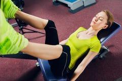 Νέα γυναίκα που κάνει την άσκηση για τα πόδια στον ειδικό εξοπλισμό στη γυμναστική Στοκ φωτογραφία με δικαίωμα ελεύθερης χρήσης