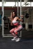Νέα γυναίκα που κάνει την άσκηση με τη στάση οκλαδόν Barbell Στοκ Εικόνες