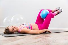 Νέα γυναίκα που κάνει την άσκηση με τη σφαίρα στοκ φωτογραφίες