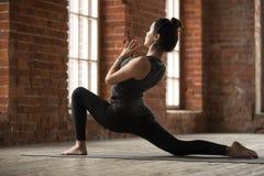 Νέα γυναίκα που κάνει την άσκηση anjaneyasana Στοκ Εικόνες
