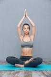 Νέα γυναίκα που κάνει την άσκηση Padmasana γιόγκας (το Lotus θέτει) Στοκ Εικόνες