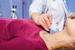 Νέα γυναίκα που κάνει την εξέταση υπερήχου λαιμών Στοκ Εικόνες