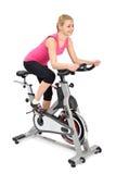 Νέα γυναίκα που κάνει την εσωτερική biking άσκηση στοκ εικόνα