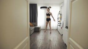 Νέα γυναίκα που κάνει την ικανότητα workout για τον υγιή τρόπο ζωής στο σπίτι o Υγιής και αθλητικός τρόπος ζωής απόθεμα βίντεο