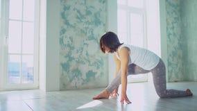 Νέα γυναίκα που κάνει την τεντώνοντας άσκηση στη γυμναστική Νέα όμορφη γιόγκα άσκησης γυναικών Έννοια Wellness Calmness και απόθεμα βίντεο