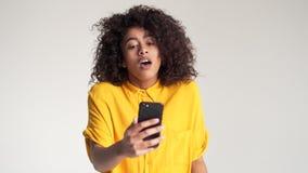 Νέα γυναίκα που κάνει την τηλεοπτική συνομιλία που χρησιμοποιεί το smartphone απόθεμα βίντεο