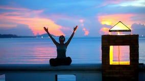 Νέα γυναίκα που κάνει τη γιόγκα και meditates πέρα από απόθεμα βίντεο