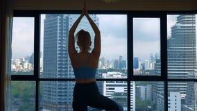 Νέα γυναίκα που κάνει τη γιόγκα σε ένα δωμάτιο κοντά σε ένα μεγάλο παράθυρο που αγνοεί τους ουρανοξύστες στοκ εικόνες