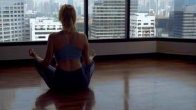 Νέα γυναίκα που κάνει τη γιόγκα σε ένα δωμάτιο κοντά σε ένα μεγάλο παράθυρο που αγνοεί τους ουρανοξύστες στοκ φωτογραφίες