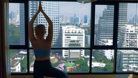 Νέα γυναίκα που κάνει τη γιόγκα σε ένα δωμάτιο κοντά σε ένα μεγάλο παράθυρο που αγνοεί τους ουρανοξύστες στοκ φωτογραφίες με δικαίωμα ελεύθερης χρήσης