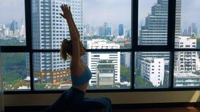Νέα γυναίκα που κάνει τη γιόγκα σε ένα δωμάτιο κοντά σε ένα μεγάλο παράθυρο που αγνοεί τους ουρανοξύστες στοκ εικόνες με δικαίωμα ελεύθερης χρήσης