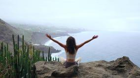 Νέα γυναίκα που κάνει τη γιόγκα στα βουνά σε ένα νησί που αγνοεί την ωκεάνια συνεδρίαση σε έναν βράχο πάνω από ένα βουνό φιλμ μικρού μήκους