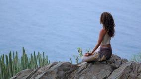 Νέα γυναίκα που κάνει τη γιόγκα στα βουνά σε ένα νησί που αγνοεί την ωκεάνια συνεδρίαση σε έναν βράχο πάνω από ένα βουνό απόθεμα βίντεο