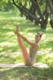 Νέα γυναίκα που κάνει τη γιόγκα στο πάρκο πρωινού Στοκ φωτογραφία με δικαίωμα ελεύθερης χρήσης