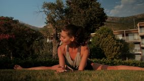 Νέα γυναίκα που κάνει τη διασπασμένη συνεδρίαση άσκησης στη χλόη το θερινό πρωί απόθεμα βίντεο