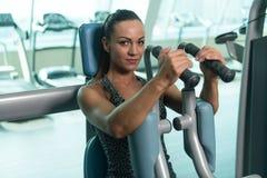 Νέα γυναίκα που κάνει τη θωρακική άσκηση στο κέντρο ικανότητας Στοκ Εικόνες