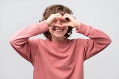 Νέα γυναίκα που κάνει τη μορφή καρδιών με τα δάχτυλα που κοιτάζουν μέσω του ματιού στοκ φωτογραφίες με δικαίωμα ελεύθερης χρήσης