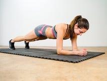 Νέα γυναίκα που κάνει τη σανίδα αγκώνων στοκ φωτογραφίες