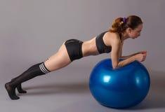 Νέα γυναίκα που κάνει τις ασκήσεις με το fitball, σε ένα γκρίζο υπόβαθρο Στοκ Φωτογραφίες
