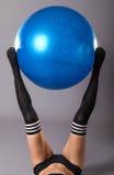 Νέα γυναίκα που κάνει τις ασκήσεις με το fitball, σε ένα γκρίζο υπόβαθρο Στοκ Φωτογραφία