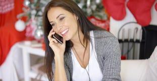 Νέα γυναίκα που κάνει τις κλήσεις Χριστουγέννων στους φίλους στοκ εικόνα με δικαίωμα ελεύθερης χρήσης