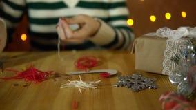 Νέα γυναίκα που κάνει το ντεκόρ για ένα χριστουγεννιάτικο δέντρο δίπλα στα κίτρινα ηλεκτρικά φω'τα φιλμ μικρού μήκους