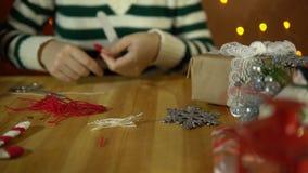 Νέα γυναίκα που κάνει το ντεκόρ για ένα χριστουγεννιάτικο δέντρο δίπλα στα κίτρινα ηλεκτρικά φω'τα απόθεμα βίντεο