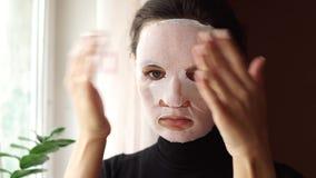Νέα γυναίκα που κάνει το του προσώπου φύλλο μασκών με τον καθαρισμό της μάσκας στο πρόσωπό της απόθεμα βίντεο
