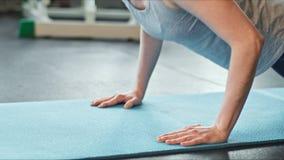 Νέα γυναίκα που κάνει το ώθηση-UPS στο χαλί άσκησης στη γυμναστική Θηλυκό που ασκεί στο χαλί ικανότητας στη γυμναστική φιλμ μικρού μήκους