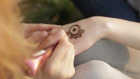 Νέα γυναίκα που κάνει το floral mehendi σε ετοιμότητα που χρησιμοποιεί henna φιλμ μικρού μήκους