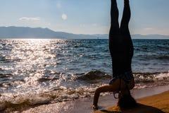 Νέα γυναίκα που κάνει Handstand στην άμμο Στοκ εικόνα με δικαίωμα ελεύθερης χρήσης