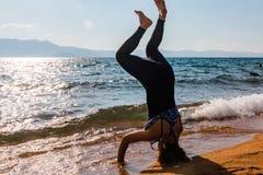 Νέα γυναίκα που κάνει Handstand στην άμμο Στοκ φωτογραφία με δικαίωμα ελεύθερης χρήσης