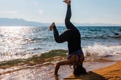 Νέα γυναίκα που κάνει Handstand στην άμμο Στοκ εικόνες με δικαίωμα ελεύθερης χρήσης