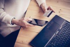 Νέα γυναίκα που κάνει on-line να ψωνίσει από το lap-top και το smartphone στη θέση εργασίας Κορίτσι σχετικά με το εγχώριο κουμπί  Στοκ Φωτογραφία