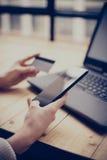Νέα γυναίκα που κάνει on-line να ψωνίσει μέσω του lap-top και του smartphone Κορίτσι σχετικά με το εγχώριο κουμπί στο κινητό τηλέ Στοκ Φωτογραφίες
