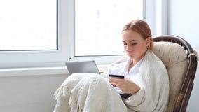 Νέα γυναίκα που κάνει on-line να ψωνίσει στο lap-top στο σπίτι απόθεμα βίντεο