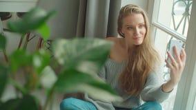 Νέα γυναίκα που κάνει selfie καθμένος κοντά σε ένα παράθυρο στο σπίτι φιλμ μικρού μήκους
