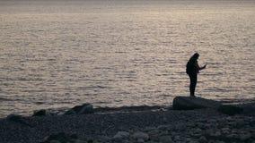 Νέα γυναίκα που κάνει selfie στεμένος στην παραλία με το smartphone και τα ακου φιλμ μικρού μήκους
