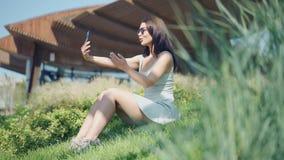 Νέα γυναίκα που κάνει selfie τη συνεδρίαση στην πράσινη χλόη φιλμ μικρού μήκους