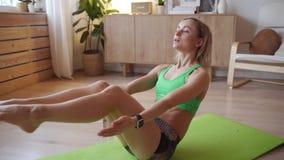 Νέα γυναίκα που κάνει workout στο σπίτι Καυκάσια γυναίκα που κάνει bodyweight τις ασκήσεις στο χαλί γιόγκας φιλμ μικρού μήκους