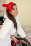 Όμορφη γυναίκα που καθαρίζει έξω τον καναπέ Στοκ Εικόνες