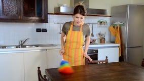 Νέα γυναίκα που καθαρίζει τα έπιπλα στην κουζίνα απόθεμα βίντεο
