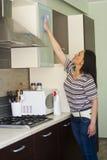 Νέα γυναίκα που καθαρίζει τα έπιπλα Στοκ Εικόνες