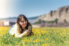Νέα γυναίκα που καθορίζει χρησιμοποιώντας το κινητό τηλέφωνο στοκ εικόνες