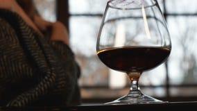 Νέα γυναίκα που καλύπτεται στο καρό που θερμαίνει με το ποτήρι του κονιάκ, χειμερινή διάθεση φιλμ μικρού μήκους