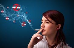 Νέα γυναίκα που καπνίζει το επικίνδυνο τσιγάρο με τα σημάδια απαγόρευσης του καπνίσματος Στοκ φωτογραφία με δικαίωμα ελεύθερης χρήσης